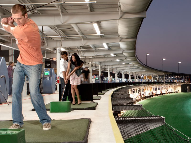 At TopGolf's modern driving range, golf balls are embedded with computer chips, and players earn points by aiming for various targets.
